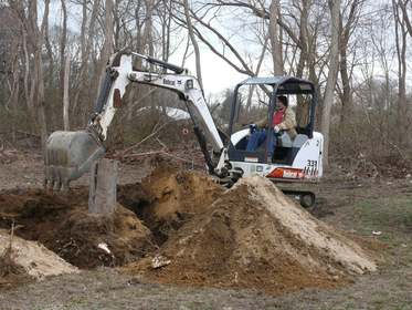Tracked backhoe stump removal